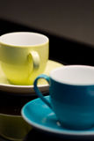 Close-up of 2 coffee cups. Close-up of 2 colored coffee ups on a black tray with a dark background Stock Image