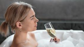 Close-up aanbiddelijke glimlachende jonge vrouw die nemend bad het drinken champagne zijaanzicht ontspannen stock video