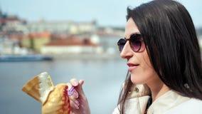 Close-up aanbiddelijke glimlachende vrouw die in zonnebril roomijs eten die op dijk lopen die van onderbreking genieten stock videobeelden