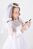 Young girl's First Communion. A close-up, from above, of a young girl smiling in her First Communion Dress and Veil, reading a bible while holding her rosary Royalty Free Stock Photo
