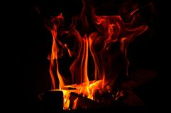 Close up. Abstrack background. Burning wood in the fireplace. Red-orange flame flutters in the dark. Copy space