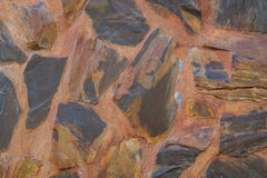 Abstract background wall made of rough stones black and brown Stock Photography