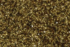Gold glitter. Close up abstract photograph of sparkly, metallic and reflective gold glitter stock images