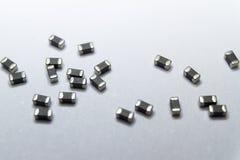 Close-up abstrato de cinzento dispersado 0402 componentes da eletrônica de poder do grânulo de ferrite da microplaqueta da montag fotos de stock