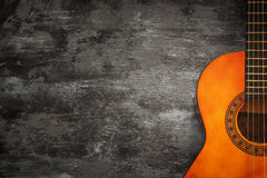 Close up of acoustic guitar against a wooden background.  royalty free stock photo