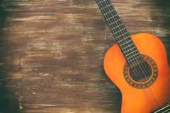 Close up of acoustic guitar against a wooden background.  Stock Photography