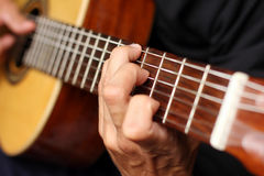 Close up acoustic guitar in musician hands Stock Image