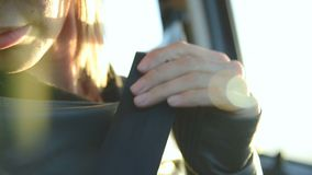 Close-up of action girl fastens a seat belt in a car before dropping off. Safe driving concept