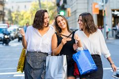 Threesome girl friends having fun shopping in city. stock photos