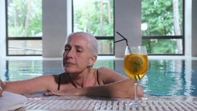 Mature woman swimming to pool side in spa hotel stock video footage