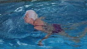 Happy elderly woman swimming in pool of spa hotel