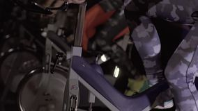 Close-up of active people using exercise bike to train stock footage