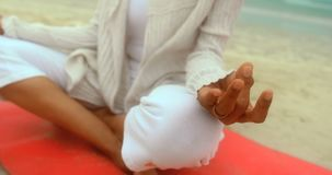Close-up of active senior African American woman doing yoga on exercise mat at the beach 4k. Close-up of active senior African American woman doing yoga on stock footage