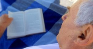 Close-up of active senior Caucasian man reading a book on the beach 4k. Close-up of active senior Caucasian man reading a book on the beach. He is relaxing on stock video footage