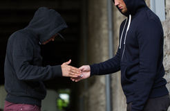 Close up of addict buying dose from drug dealer. Drug trafficking, crime, addiction and sale concept - close up of addict buying dose from dealer Royalty Free Stock Images