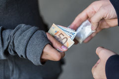 Close up of addict buying dose from drug dealer. Drug trafficking, crime, addiction and sale concept - close up of addict with money buying dose from dealer on Royalty Free Stock Photos