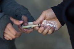 Close up of addict buying dose from drug dealer. Drug trafficking, crime, addiction and sale concept - close up of addict with money buying dose from dealer on Stock Images