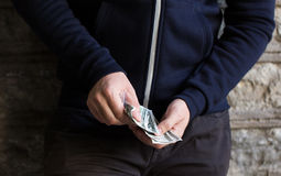 Close up of addict or drug dealer hands with money Royalty Free Stock Photography