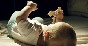 Close-up of adorable curious baby playing with wooden toy in the bed. Little baby playing with wooden toys at night in. Dark room stock footage