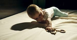 Close-up of adorable curious baby playing with wooden toy in the bed. Little baby playing with wooden toys at night in. Dark room stock video