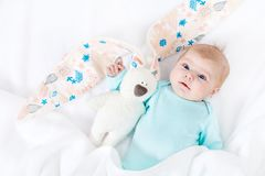 Adorable cute newborn baby girl with Easter bunny toy. Close-up of adorable cute newborn baby girl of two months on white background. Lovely child playing with Stock Image