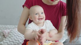 Joyful baby playing in palms with mother at home stock video