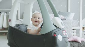 Joyful baby looking up sitting in toy car at home stock footage