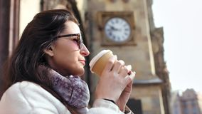 Close-up adorable young woman relaxing drinking coffee surrounded by beautiful medieval architecture. At sunset. Side view happy travel girl in sunglasses stock video