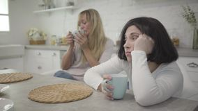 Close-up of adult brunette Caucasian woman siting with coffee cup at the table. Her blond female friend drinking hot