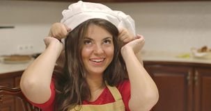 Close-up of adult caucasian woman looking at camera and smiling. Little girl putting cook hat on the head of mother stock video