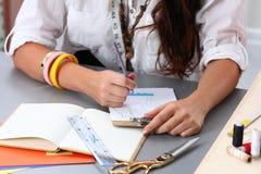 Close-up of adult female dressmaker drowing some clothing design Stock Image