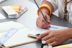 Close-up of adult female dressmaker drowing some clothing design Stock Images