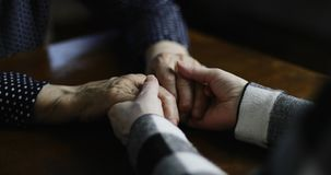 Close-up of adult hands stroking senior female hands with deep wrinkles. Tenderly comforting an elderly woman at the hospital stock video
