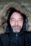 Close up Adult Man in Fur Lined Hooded Coat. Close up Smiling Face with Beard and Mustache of an Adult Man Wearing Black Fur Lined Hooded Coat Royalty Free Stock Photos