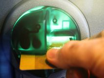 Man`s hand inserting a debit card into the slot of an automatic stock image