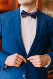 Close-up adult solid man button his blue suit near window Royalty Free Stock Photo
