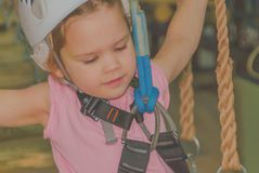Close up , the adventure Park the kid in the white helmet and in. Girl in a white helmet and insurance in adventure Park, closeup Royalty Free Stock Photo