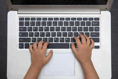 Close up aerial view of children hands typing on laptop Royalty Free Stock Photo