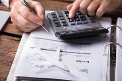 Close-up Of An Aeroplane On Invoice. Close-up Of A White Aeroplane In Front Of Businessperson Calculating Invoice stock photo
