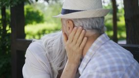 Close-up of affectionate senior couple talking. Close-up of affectionate senior couple sitting outdoors, talking about love, flirting and kissing. Beautiful stock video footage