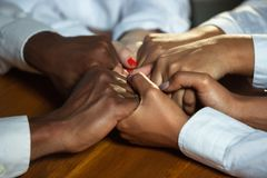 Close up of african-american and caucasian human`s hands holding on wooden table