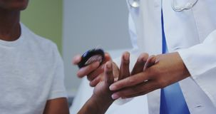 Close-up of African american female doctor checking sugar level of male patient in hospital ward stock footage
