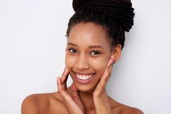 Close up african american female fashion model with hands by face against white background. Close up portrait of african american female fashion model with hands royalty free stock photos
