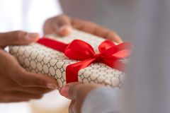 Close up African American female hands holding gift box. Teenage girl congratulating mother with mothers day or birthday, black mom receiving present from stock photo