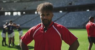 Male rugby player standing with hands on hip in stadium 4k. Close-up of African American male rugby player standing with hands on hip in stadium. He is tired and stock video