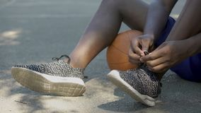 Close-up of African-American man legs, basketball player tying shoelaces. Stock footage stock video