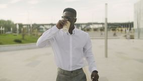 Close up of African American man wearing white shirt drinking coffee and using his phone stock video