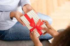 Close up African American teen girl presenting gift to mother. Close up African American teen girl presenting gift box to mother, teenage daughter making royalty free stock images