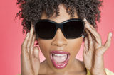 Close-up of an African American woman wearing sunglasses over colored background stock photos