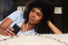Close up african american young woman with smart phone and earphones. Close up african american young woman lying on floor with smart phone and earphones Royalty Free Stock Photo
